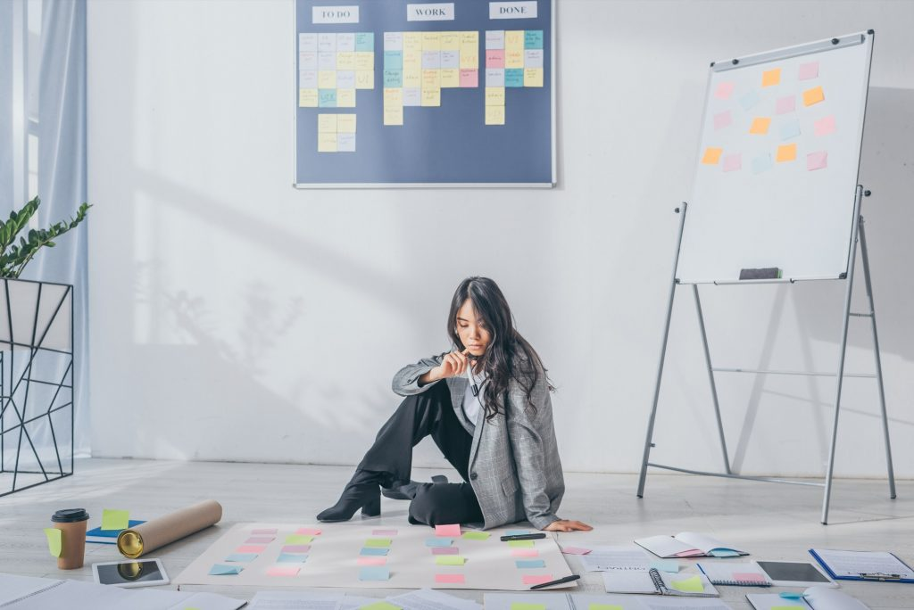 beautiful asian scrum master sitting on floor near gadgets and sticky notes