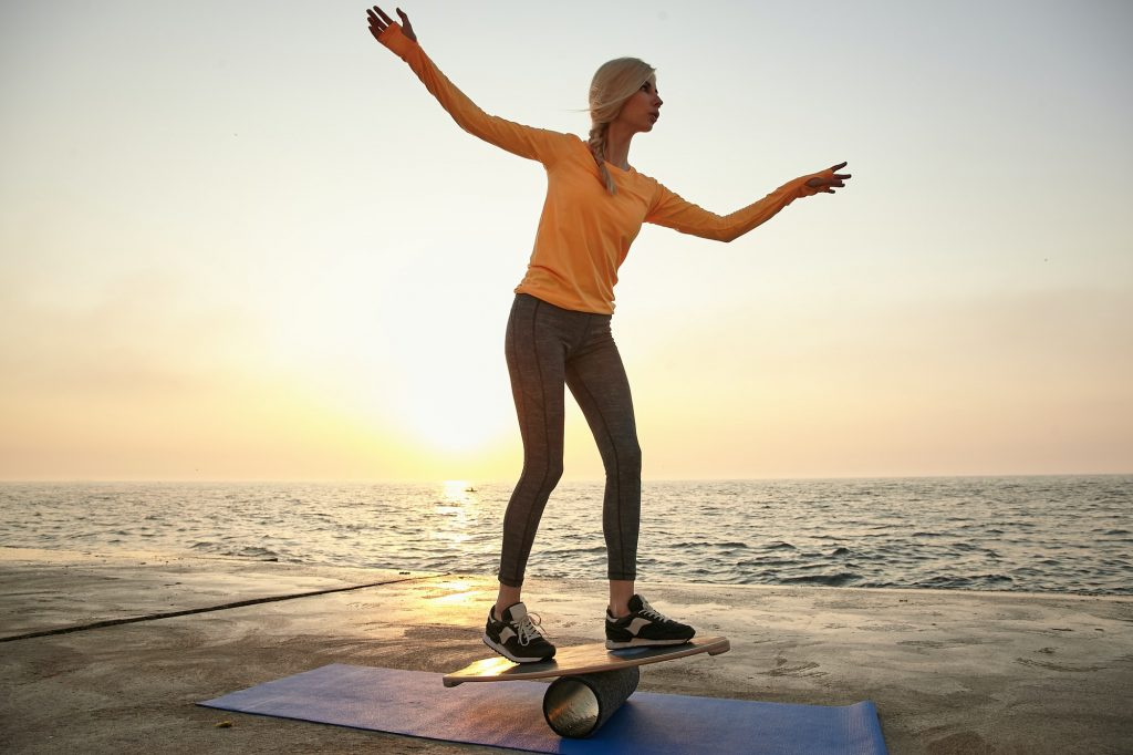 Outdoor shot of young lovely woman trying to keep balance on wooden desk, balancing