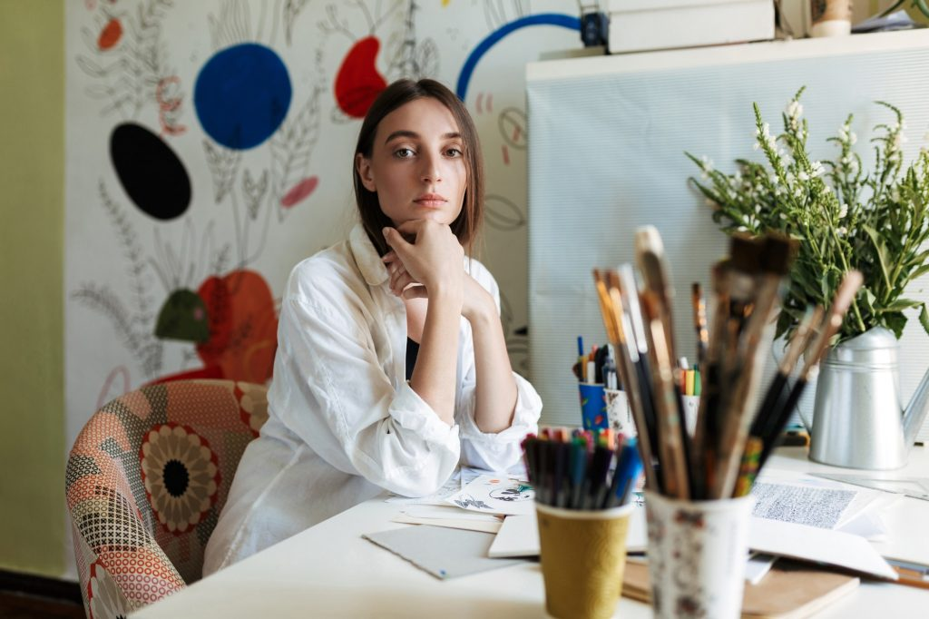 Young painter in white shirt at the desk thoughtfully looking in